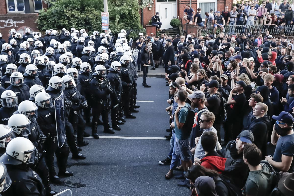 Protestors (R) and policemen stand face to face during the demonstration 'Welcome to Hell' ahead of the G20 summit in Hamburg, Germany, 06 July 2017.