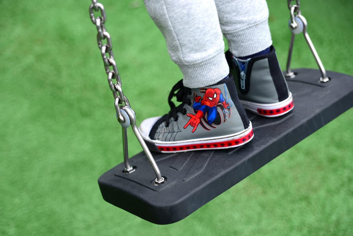 Lapsi keinuu leikkipuistossa seisoalleen.