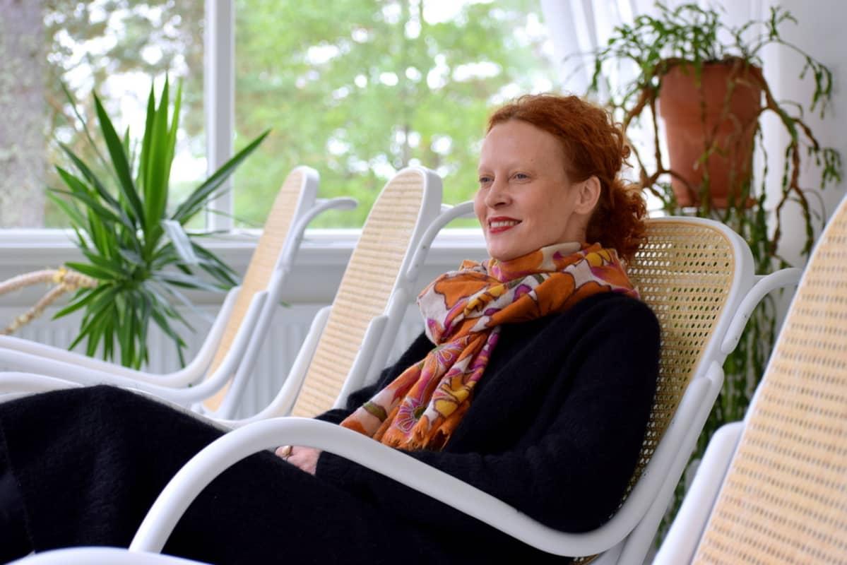 Saimi istuu hotellissaan keinutuolissa.