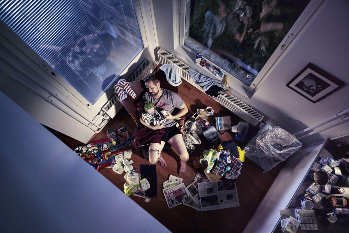 Mies pitää lasta sylissään. Kuvattu huoneiston katonrajasta. Ulkona on pimeää.