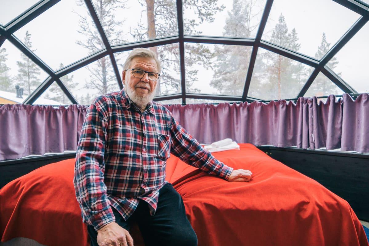 """Juhani """"Jussi"""" Eiramo lasi-iglun parisängyllä."""