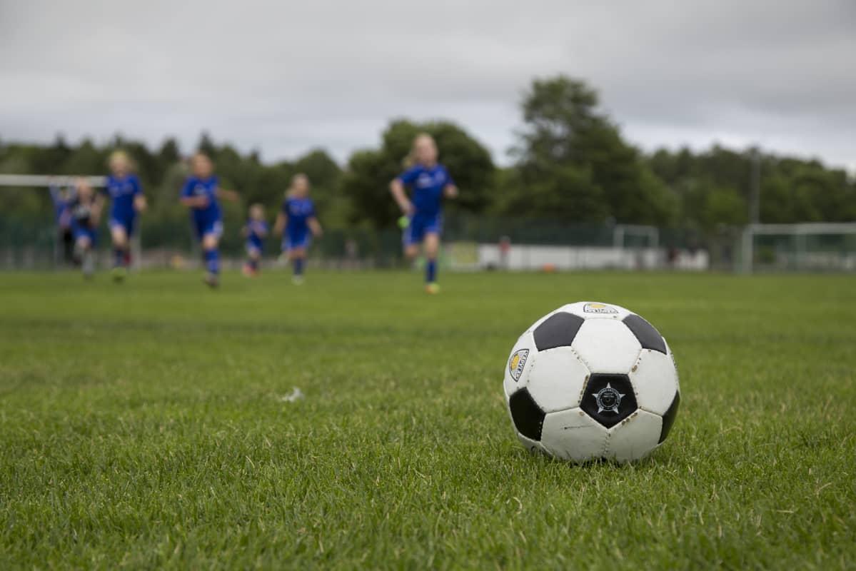 Etualalla jalkapallo ja taustalla kohti juoksevia lapsia.