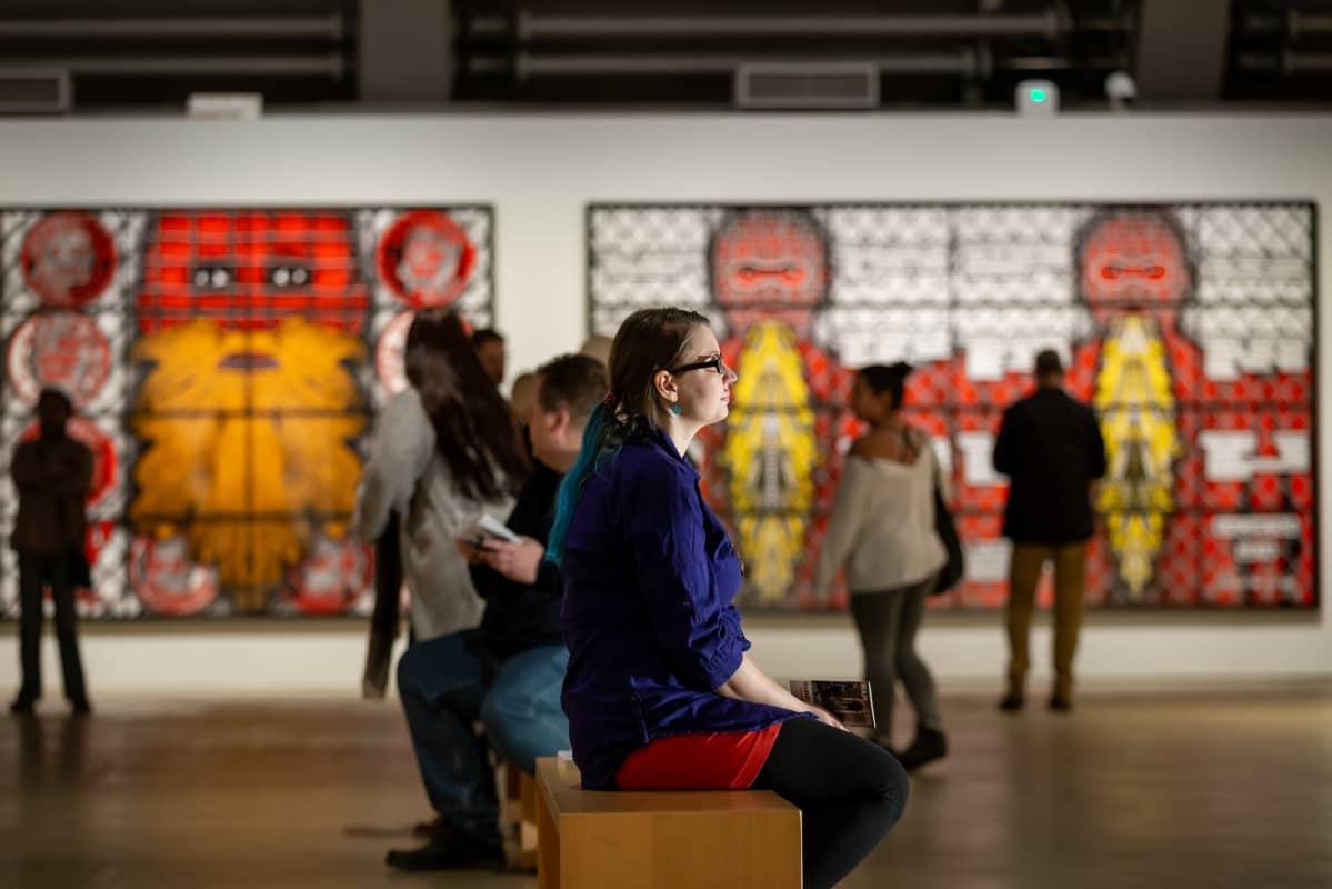 Mira Jaskari istuu ja katselee Gilbert & George -taiteilijaparin näyttelyä Helsingin taidemuseossa.