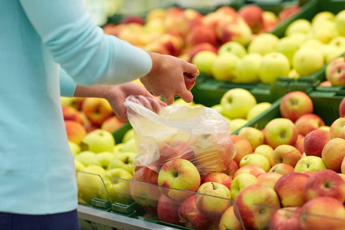 Person plockar frukter i plastpåse