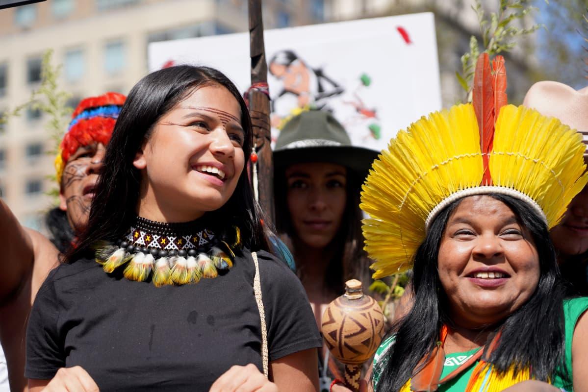 Kaksi Ecuadorin alkuperäiskansoja edustavaa naista seisoo vieretysten mielenosoituksessa värikkäissä asusteissaan.