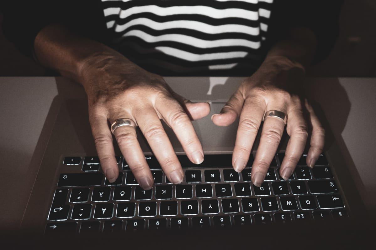 Naisen kädet kannettavalla tietokoneella.