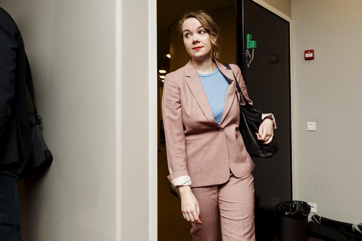 Katri Kulmuni kommer ut gåendes från en dörr.