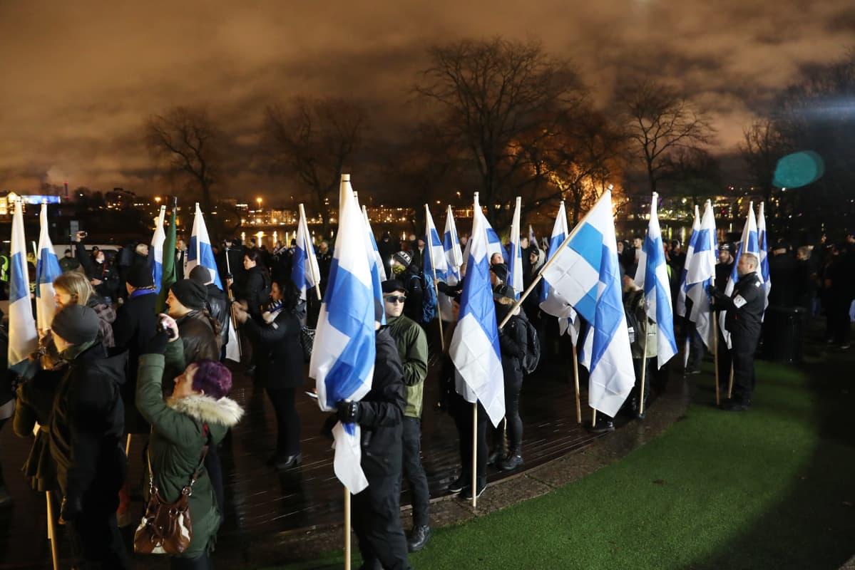 mielenosoittajia suomenlippujen kanssa