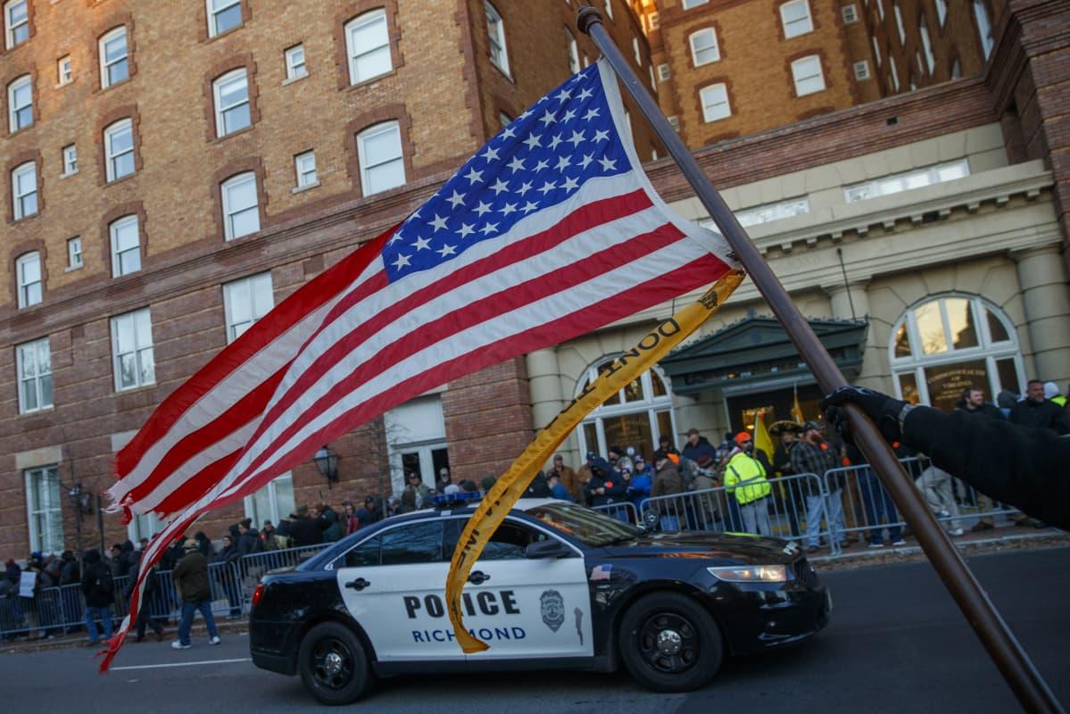 Poliisiauto ja Yhdysvaltain lippu.
