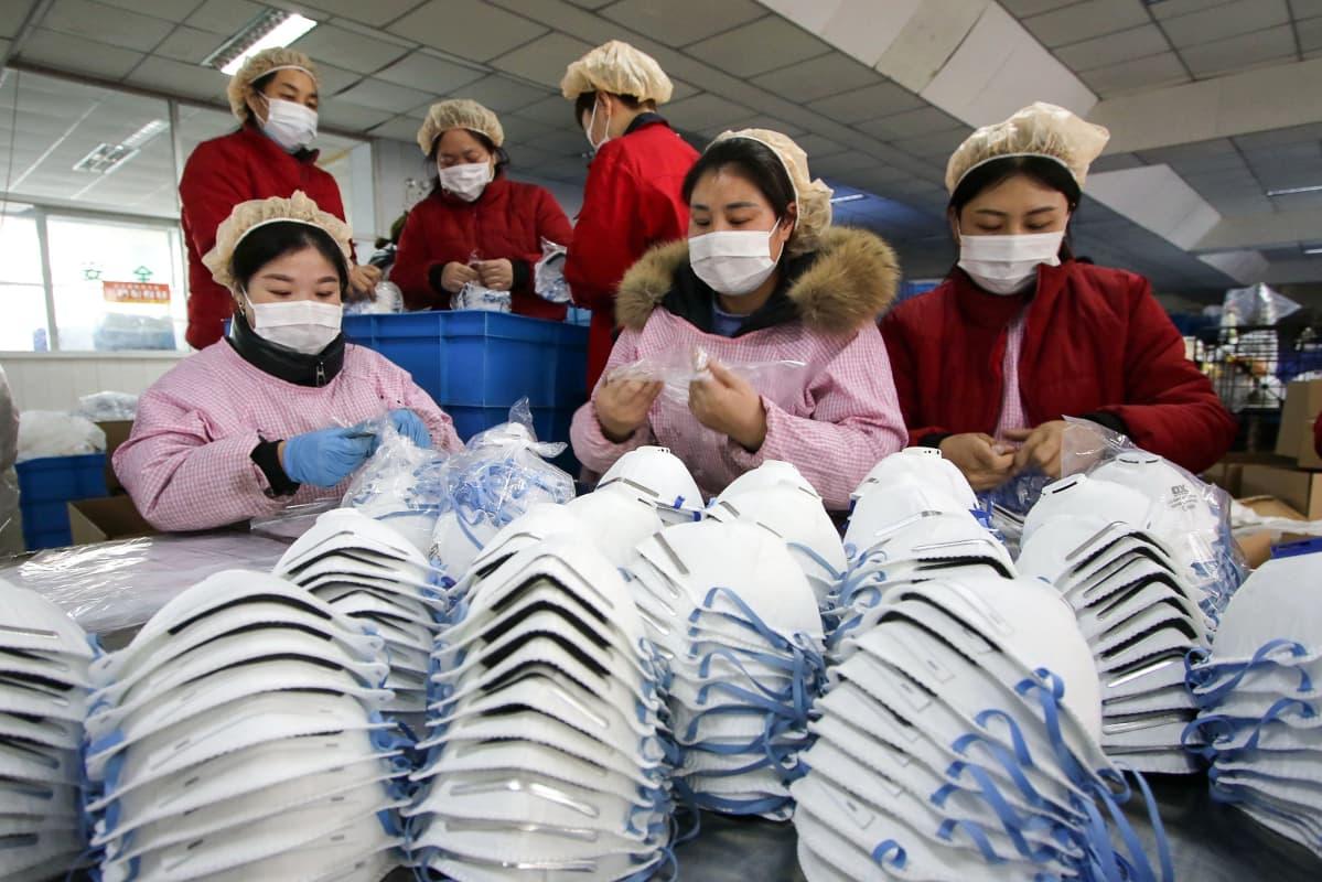 Arbetare tillverkar ansiktsmaskar i Handan i Kina. I förgrunden syns tre kvinnor och i bakgrunden tre kvinnor till. De alla bär munskydd.