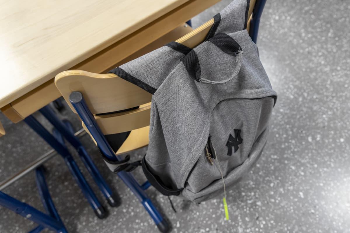 Yksinäinen koulureppu roikkuu luokassa tuolin selkänojasta.