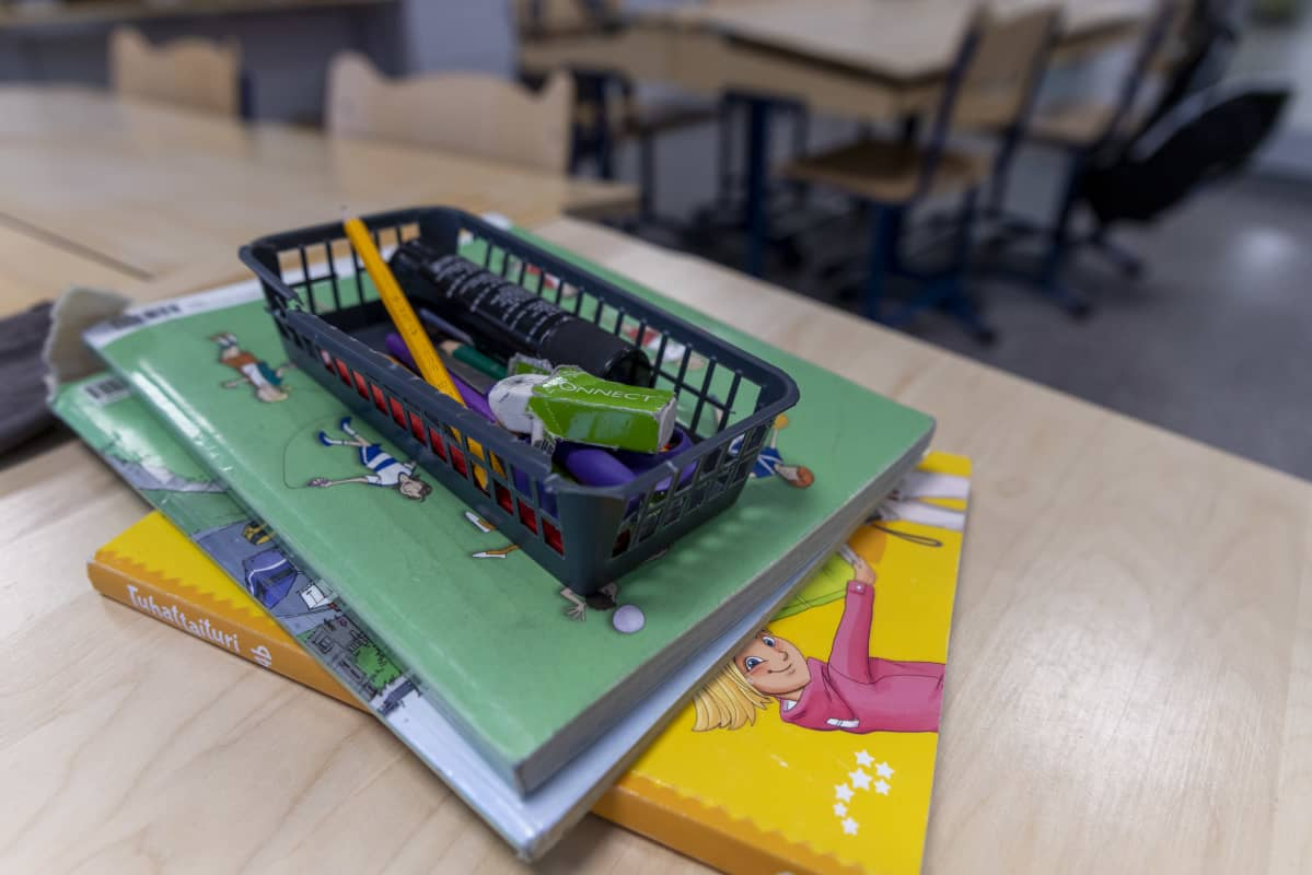 Koulukirjoja ja kynäkotelo pinossa pulpetin päällä.