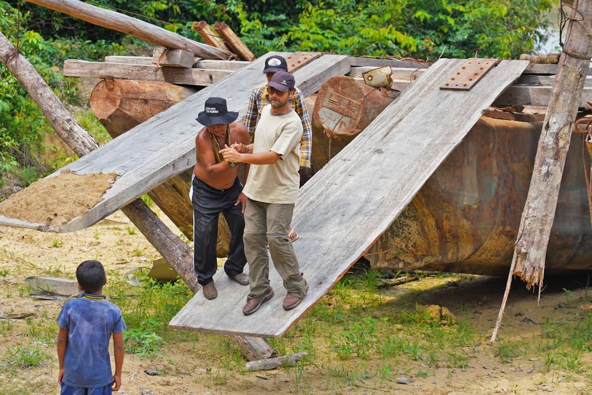 Mundurukujen tiedusteluretkikunnan jäseniä puunhakkaajien lautan ajorampilla.