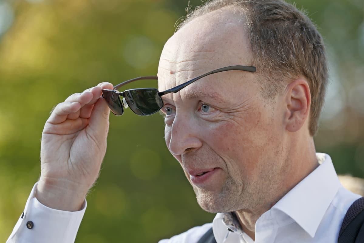 Porträttbild på Jussi Halla-aho när han tar på sig ett par svarta solglasögon.