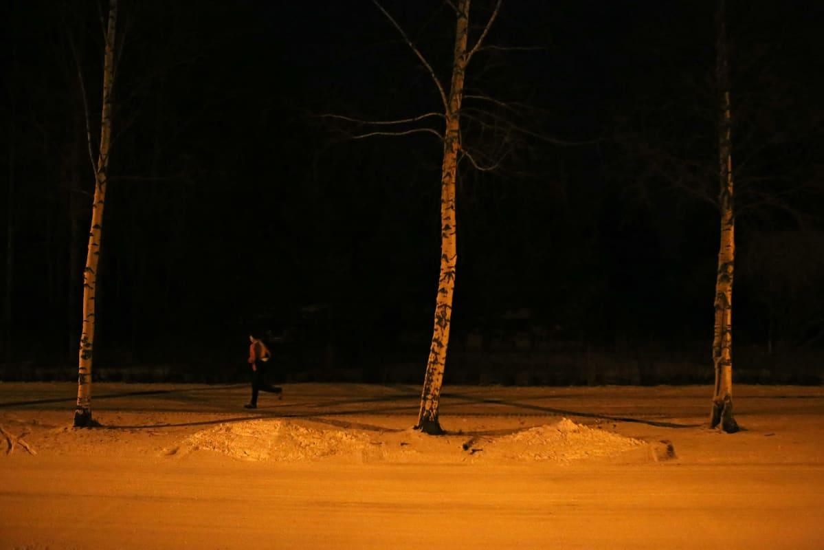 Nainen juoksee lumisella tiellä.