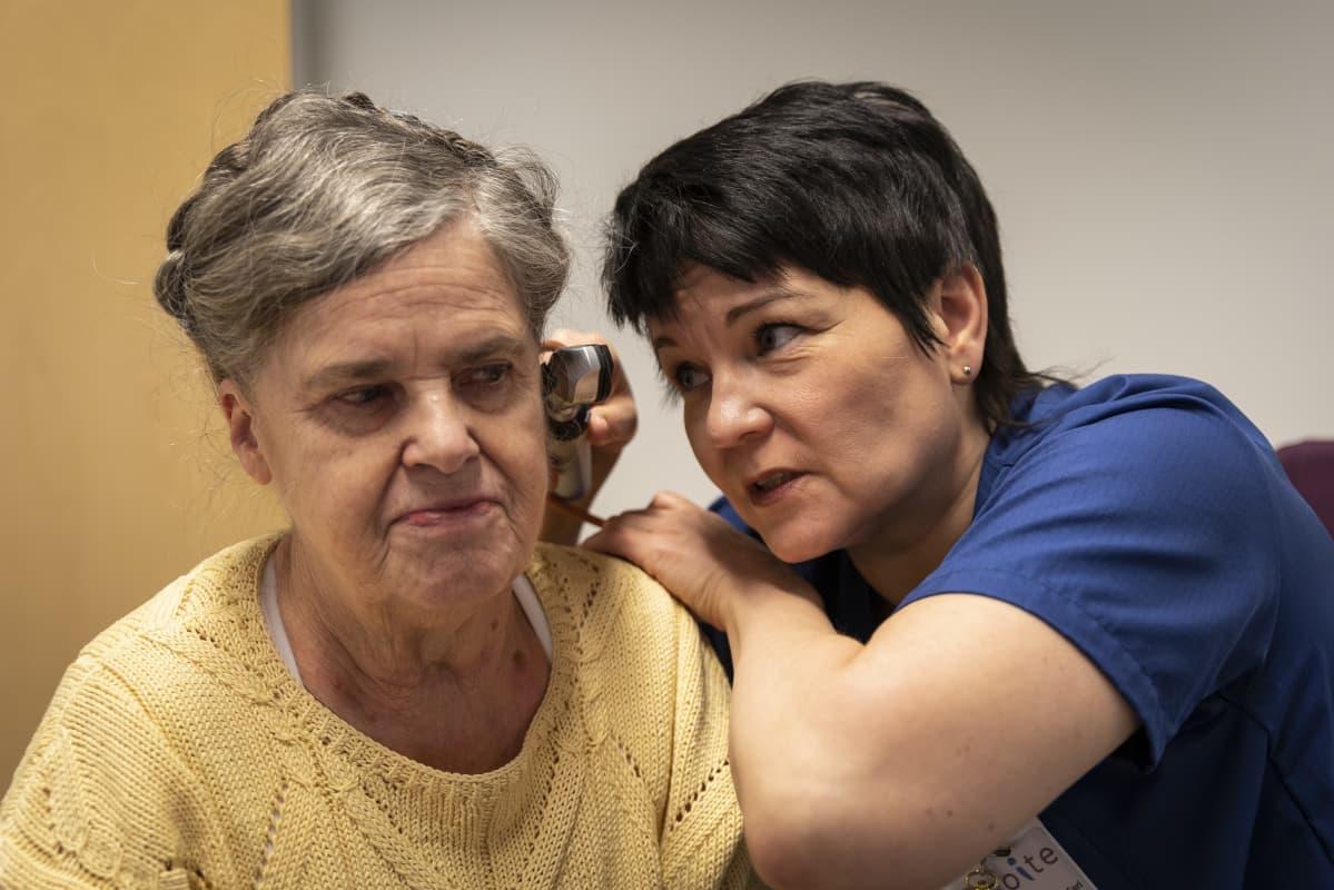 Sairaanhoitaja tutkii potilaan korvaa.