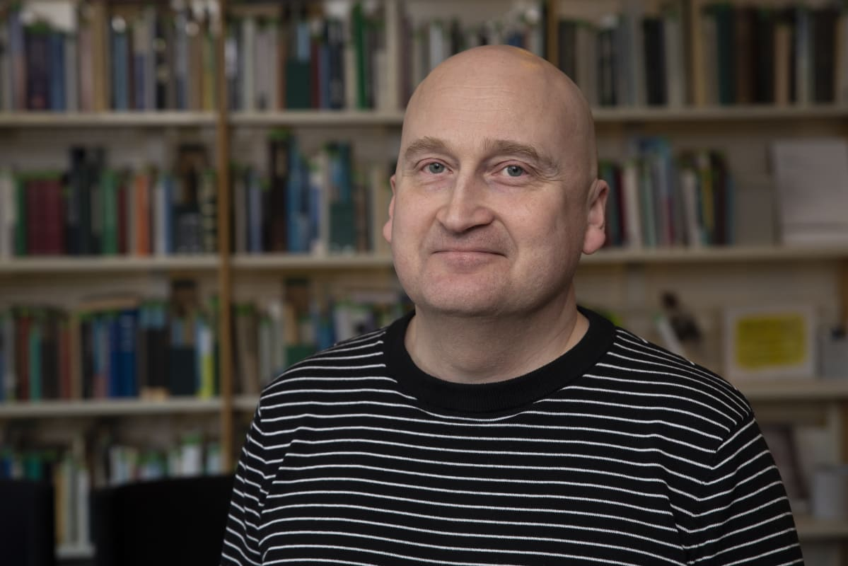 Terveyden ja hyvinvoinnin laitoksen johtava asiantuntija Thomas Karlsson kirjahyllyn edessä