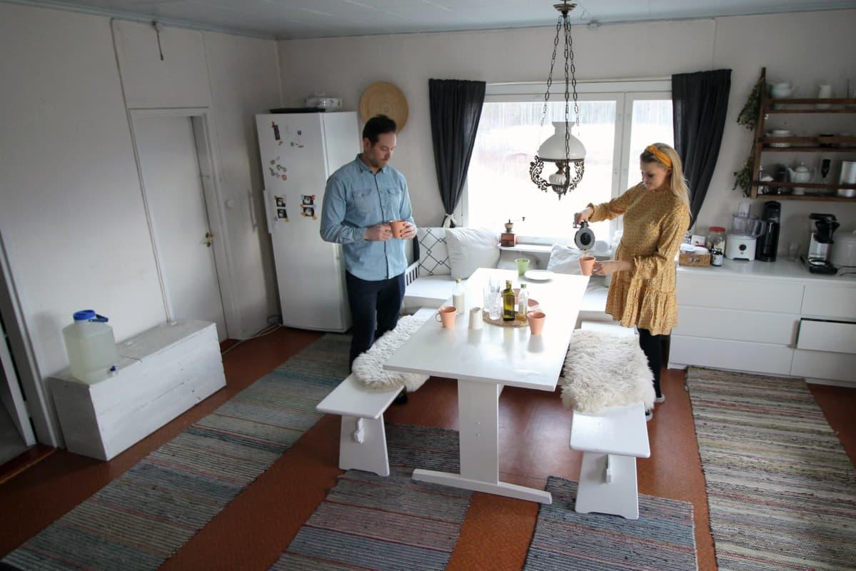 Anniina ja Juha Jalkanen tuvassa keittiön pöydän ääressä.