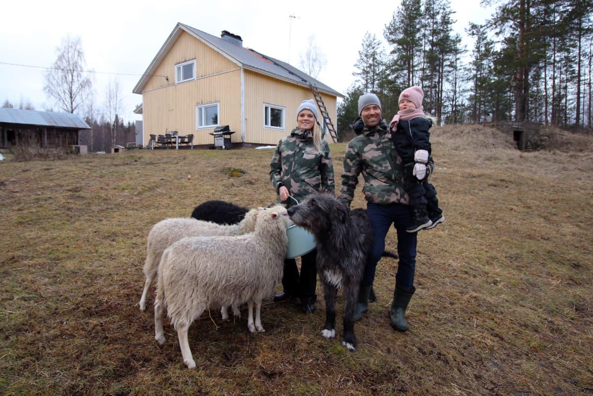 Jalkasten perhe lampaiden ympäröimänä talonsa edessä.