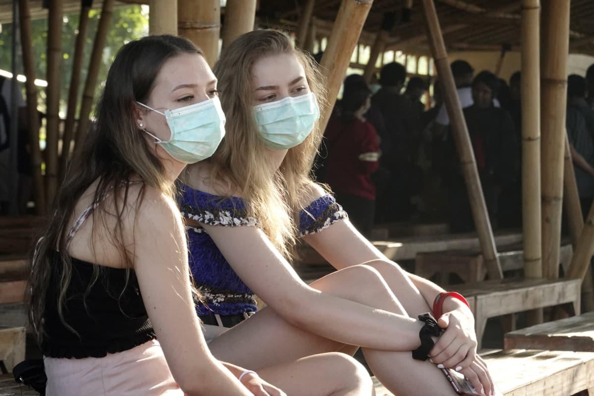 Kaksi nuorta naista istuu rannalla kasvoillaan hengityssuojaimet.