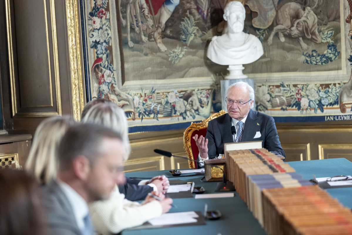 Kuningas Kaarle Kustaa istumassa pöydän päässä.