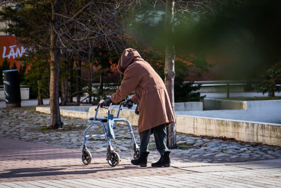 Vanhus rollaattorin kanssa kävelemässä kohti kauppaa.