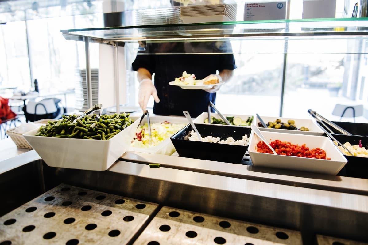 Kuvassa annostellaan lounasruokaa lautaselle.