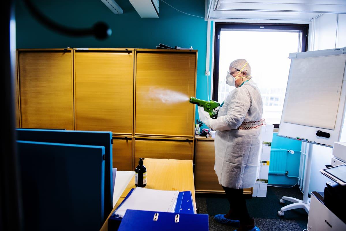 Kuvassa palvelucontroller Päivi Suojasalo puhdistaa kolmannen kerroksen toimistotiloja.