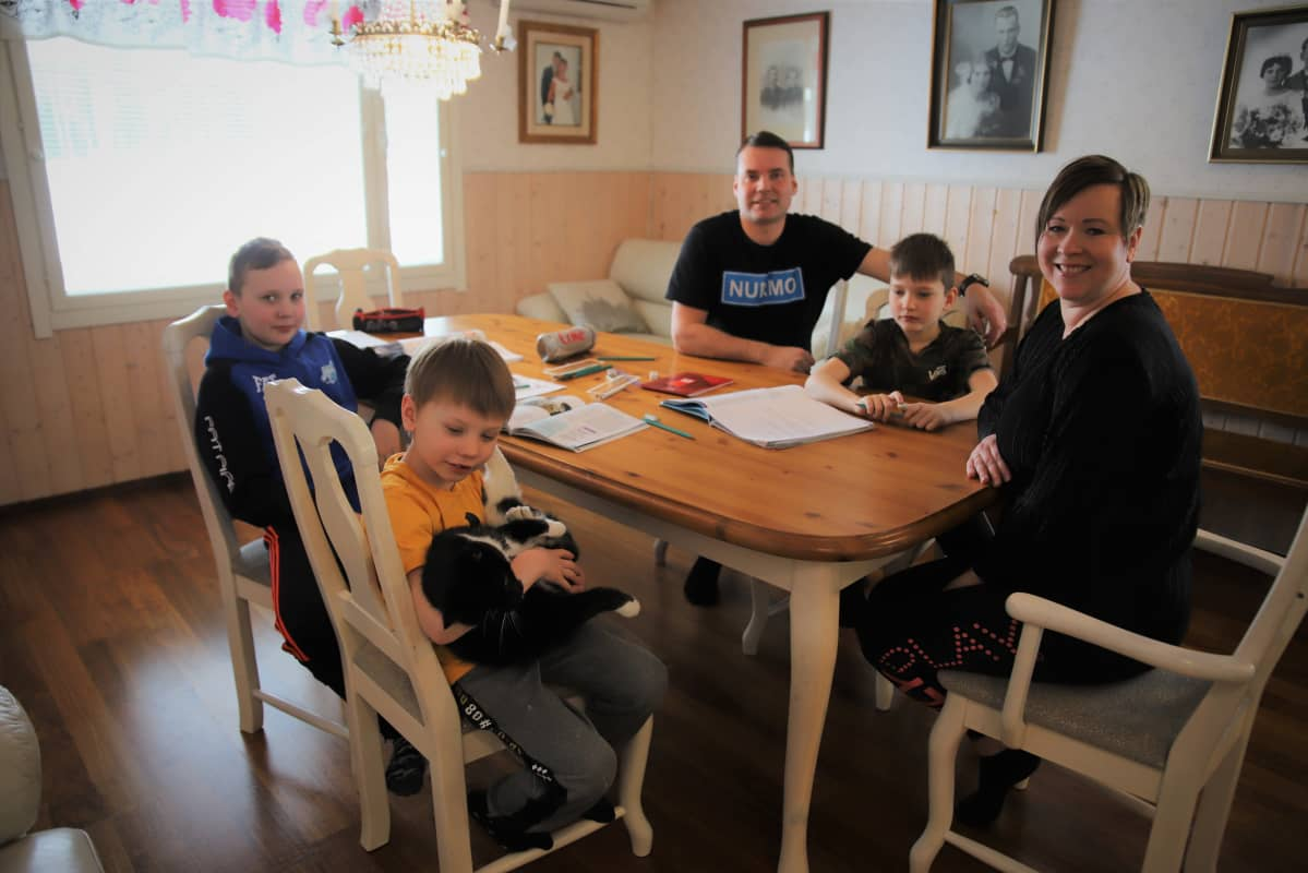Ylisen perhe istuu kotikoulun pöydän ääressä.