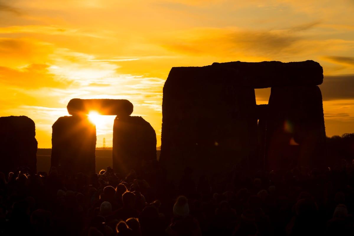 Talvipäivänseisauksen juhlijoita Stonehengellä Wiltshiressä Britanniassa auringonnousun aikaan 22. joulukuuta 2019.