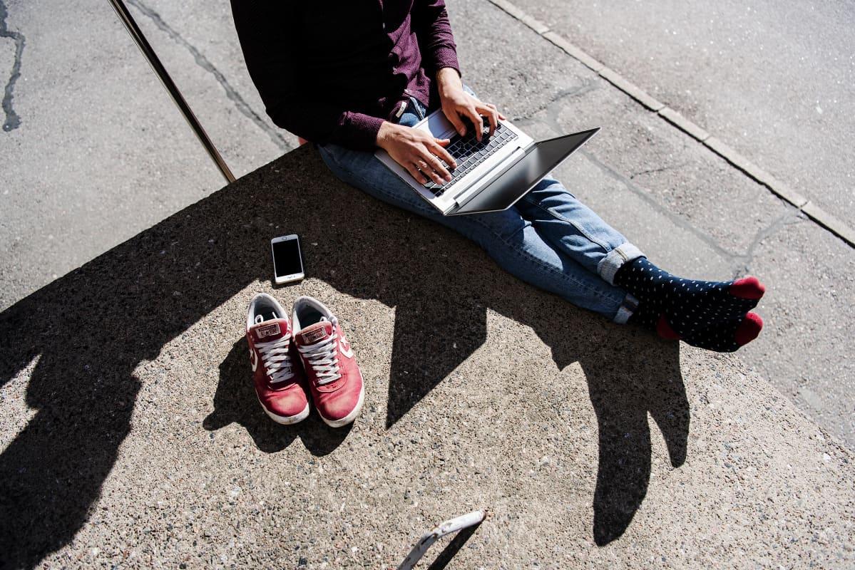 Kuvassa mies käyttää kannettavaa tietokonetta ulkona.