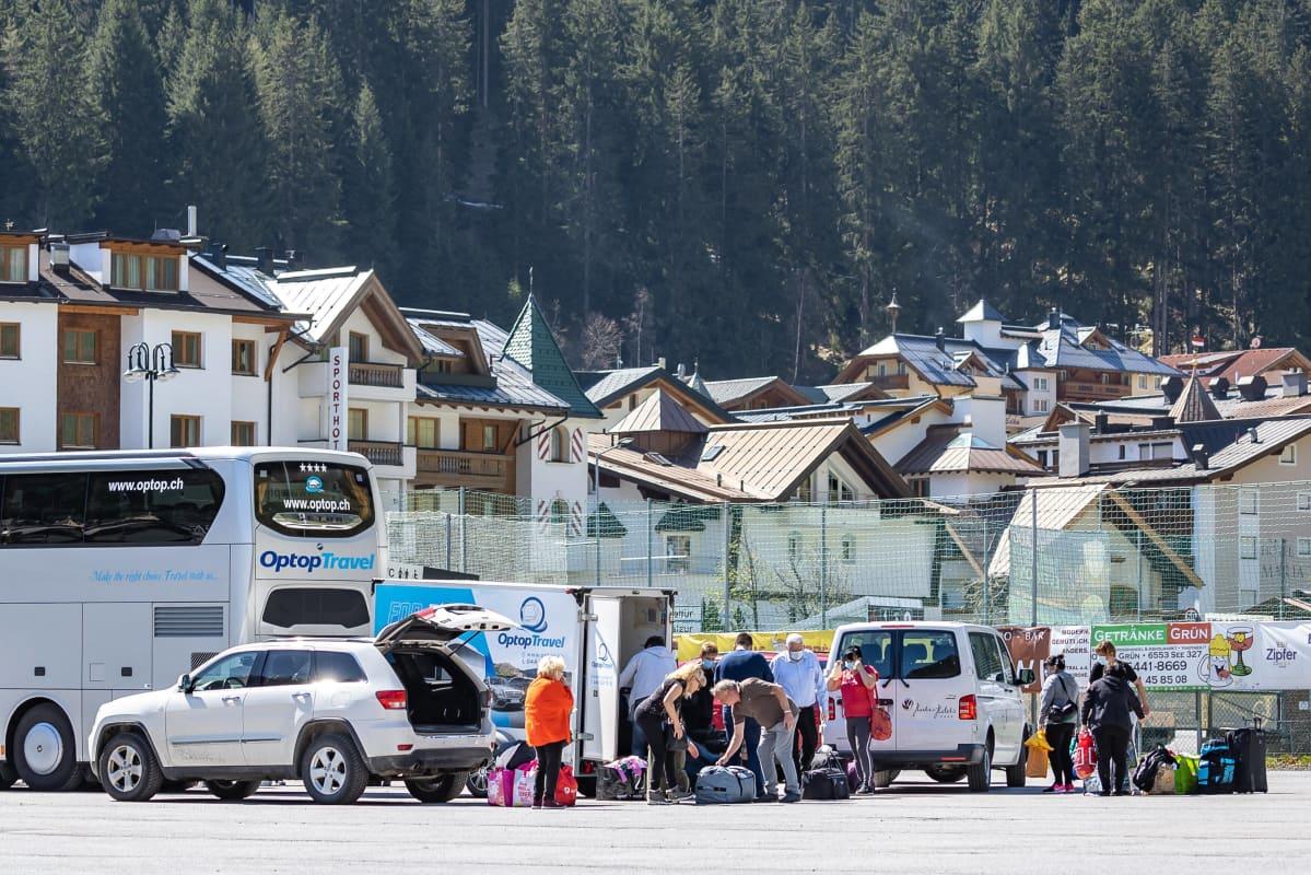 Ihmiset pakkaavat matkatavaroita tila-autoihin ja bussiin.