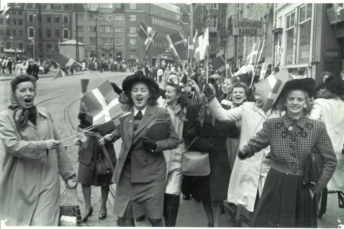 Nuoret naiset heiluttavat lippuja iloisina