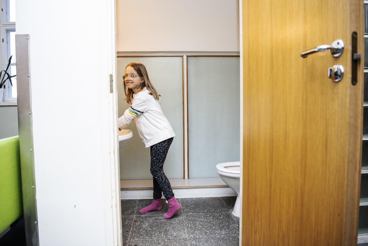 Kuvassa Selma Pihlaja pesee kädet tultuaan sisälle kouluun.