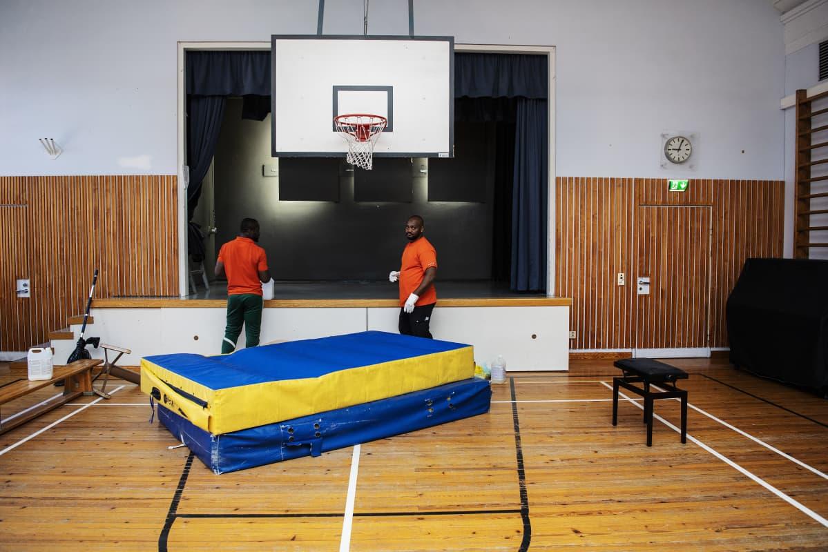 Kuvassa ovat Palmian työntekijät Derick Mbale ja Mbouk Malep Dominick, jotka tekivät koulun liikuntasalille sekä peruspesun että desinfioinnin.