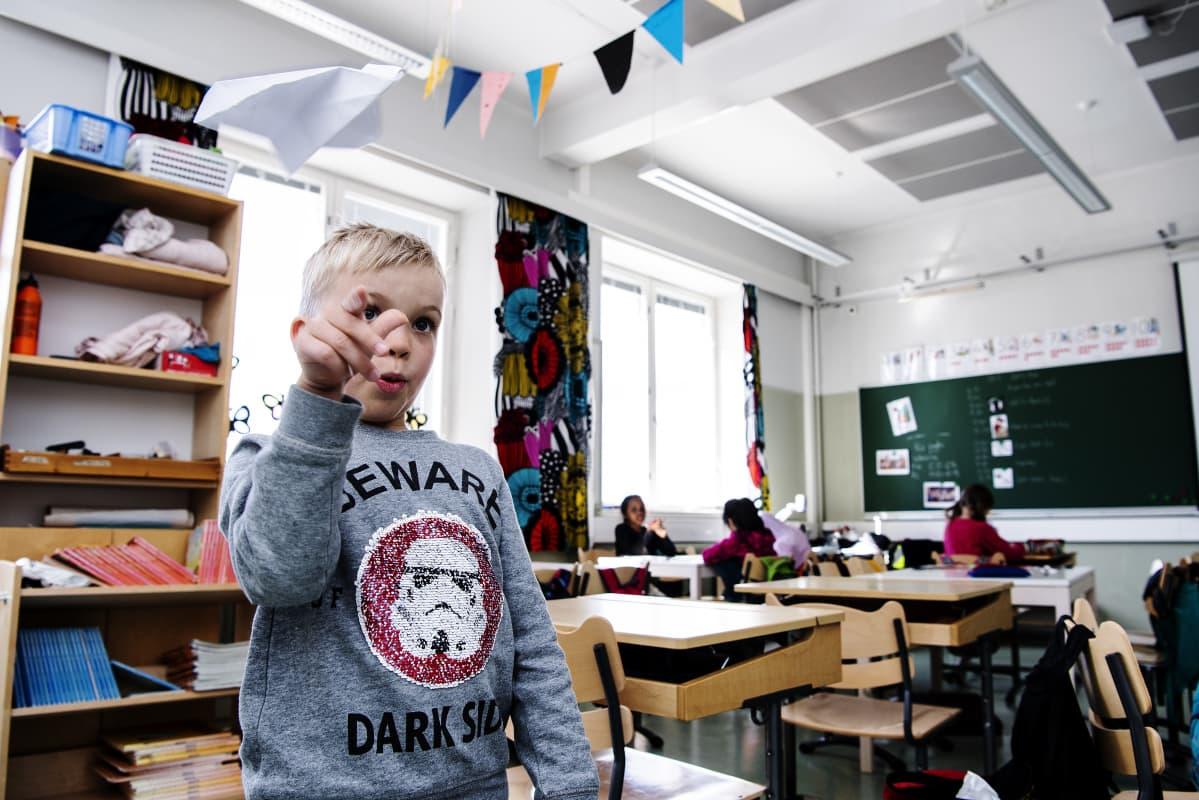 Kuvassa Ossian Eskelinen lennättää paperiliidokkia.