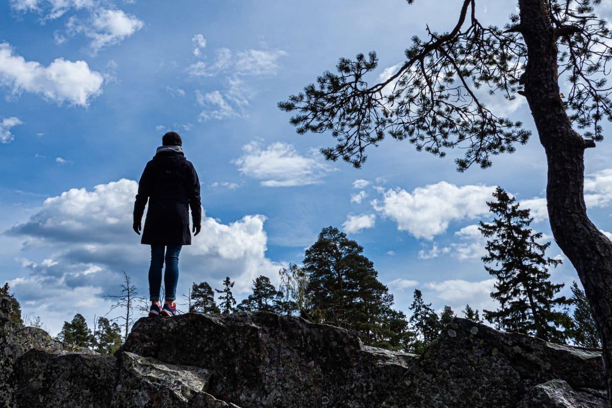 Nainen ylhäällä kalliolla katselee kohti horisonttia.