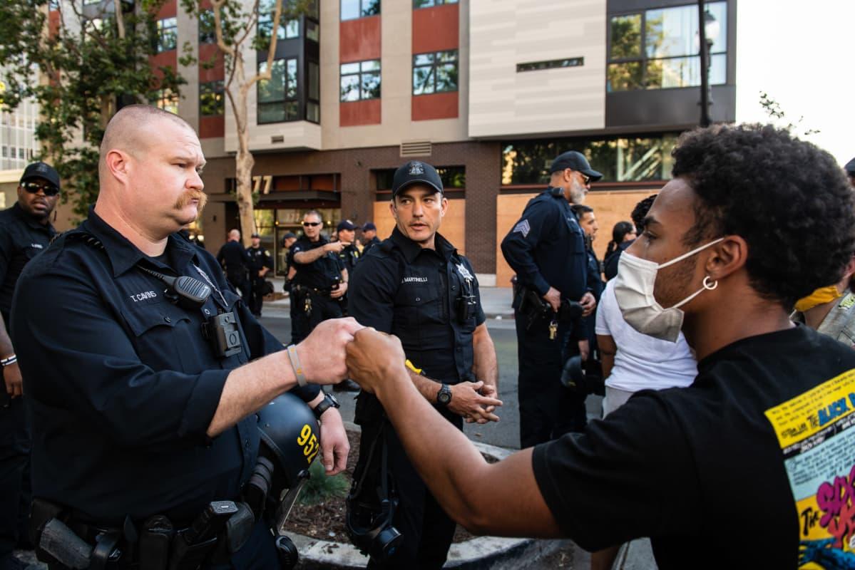 Valkoinen poliisi tekee mustan mielenosoittajan kanssa nyrkkitervehdyksen Oaklandissa, Kaliforniassa, 2. kesäkuuta 2020