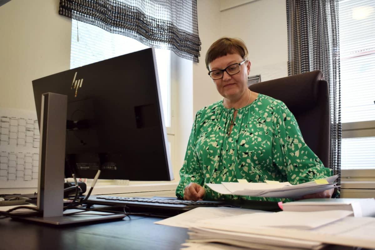 Nainen istuu työhuoneessaan työpöydän ääressä.
