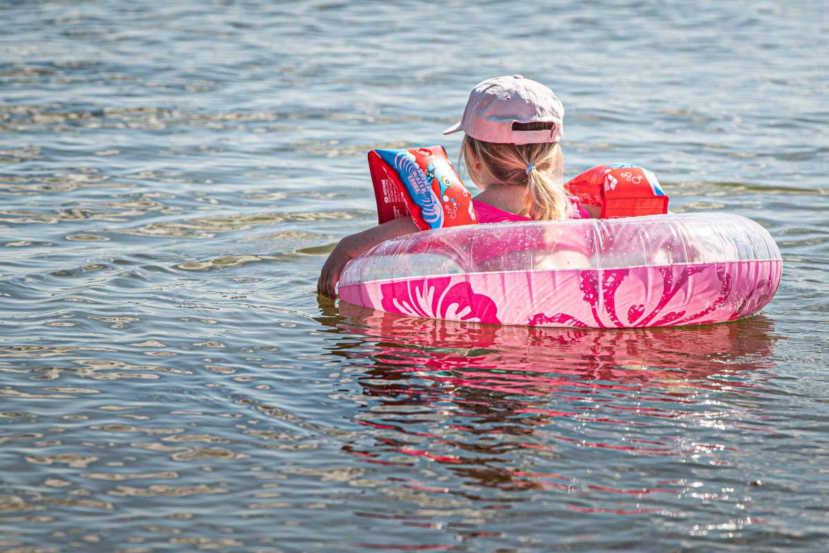 Lapsi uimassa uimarenkaan kanssa.