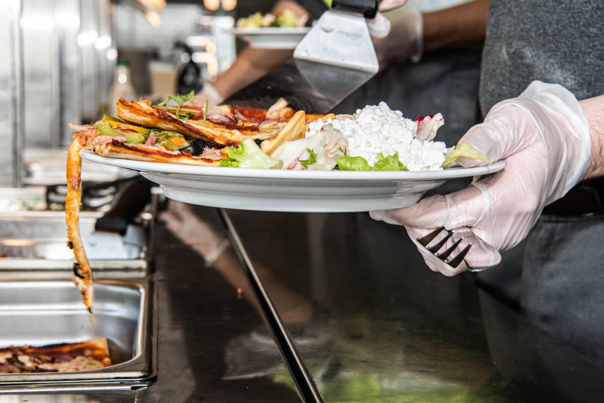 Mies ottaa ruokaa lounasravintolassa.