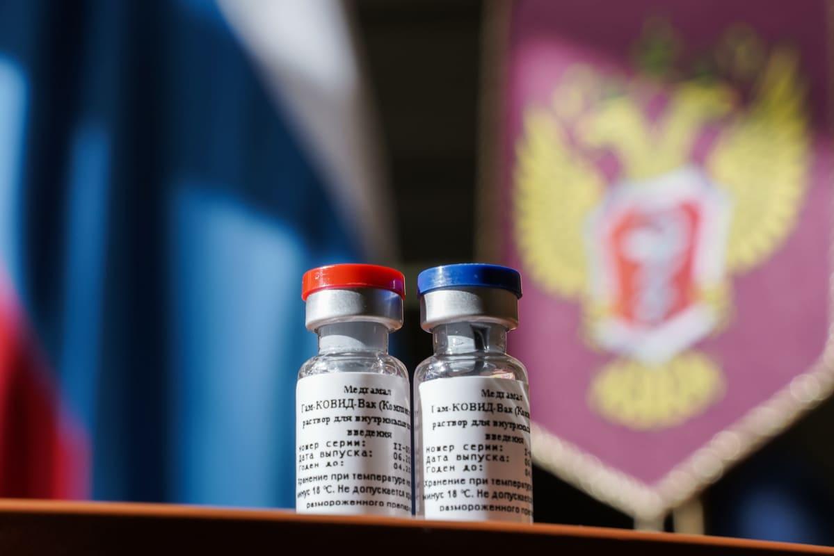 Kaksi rokotepulloa, taustalla Venäjän valtion vaakuna