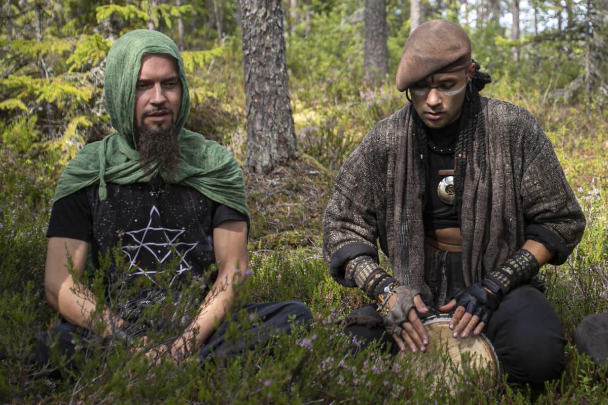 Kaksi Rainbow-leirin hippiä soittaa ja laulaa metsässä