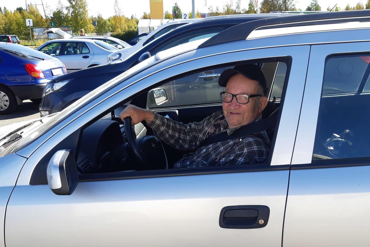 Seppo Kortelainen istuu autossaan ja katsoo kameraan.