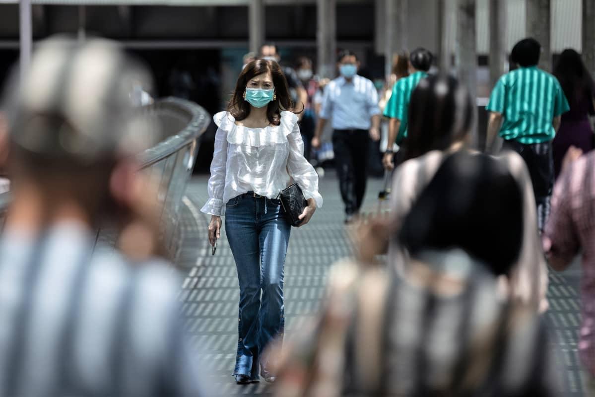 Ihmisiä kulkee kadulla maskit kasvoillaan.