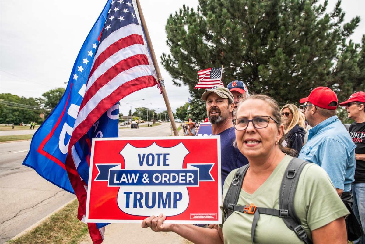 Trumpin tukija pitää kylttiä, jossa kehotetaan äänestämään Trumpia. Kyltissä lukevat sanat laki ja oikeus.