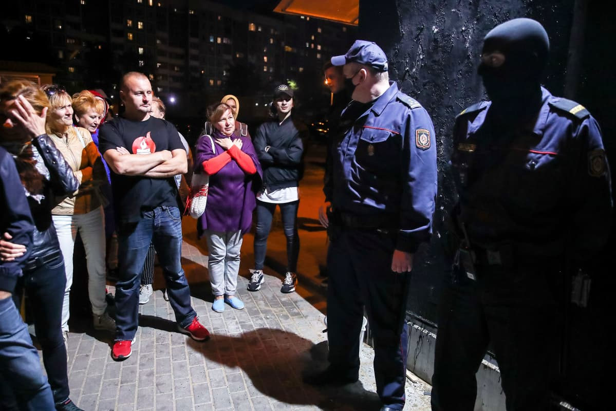 Kaksi poliisi vartioi mustaksi maalattua seinää. Protestoijat katsovat poliiseja uhmakkaasti. Toisella on päässään musta hiihtomaski, toisella kasvosuojain.