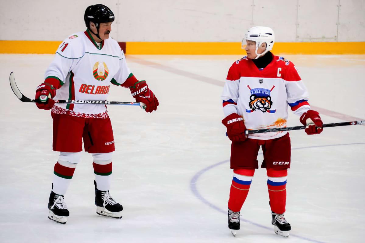 Lukašenka ja Putin ovat jääkiekkokaukalossa jääkiekkoilijan varusteissa.