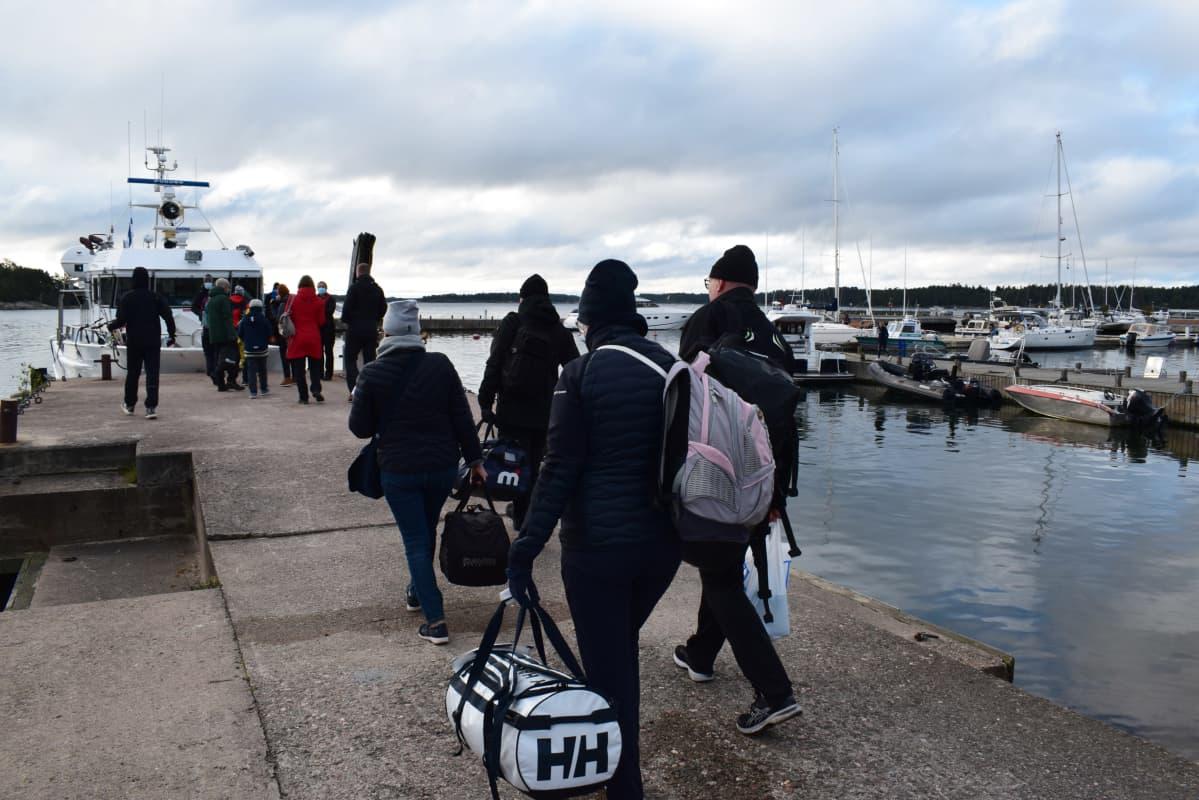 Matkalijoita menee laivaan Käsnäsin satamassa.