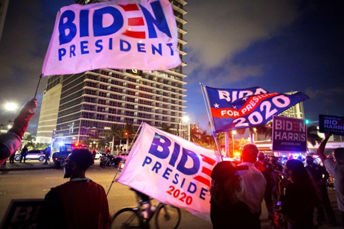 Kannattajat heiluttavat Joe Bidenia tukevia lippuja öisessä kaupunkimaisessa.